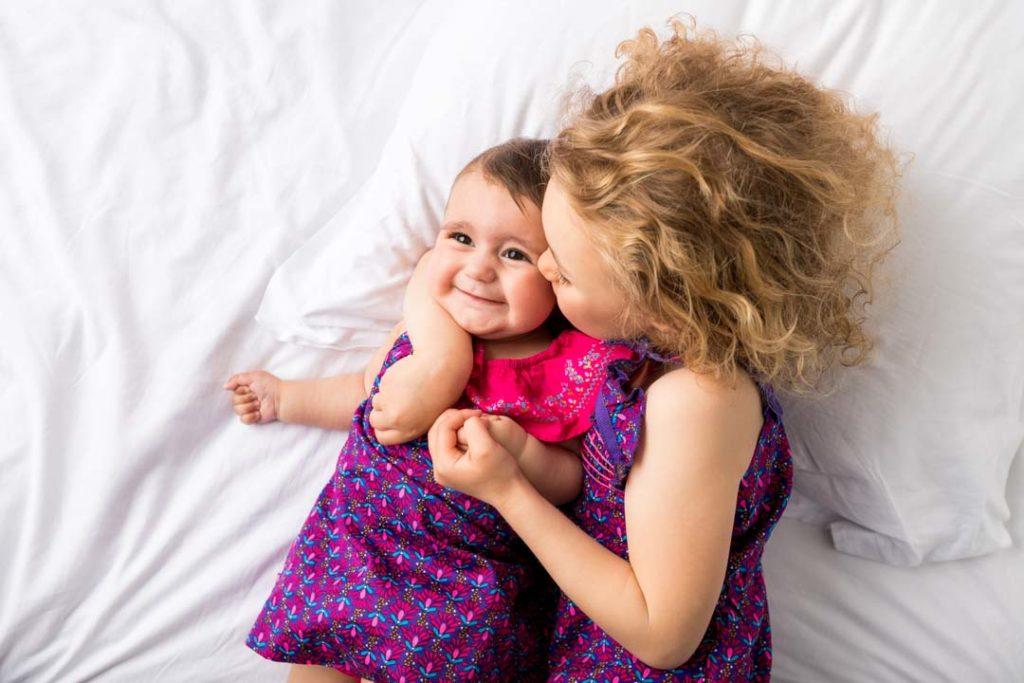 Séance photo cocooning entre sœurs sur un lit comme à la maison, dans les Yvelines