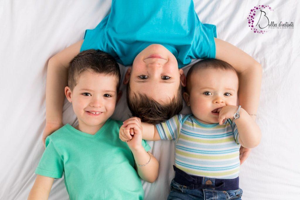 Séance photo cocooning frères sur un lit comme à la maison, dans les Yvelines
